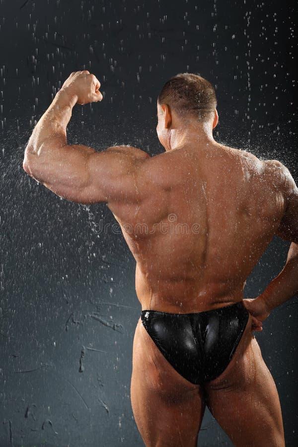 De tribunes van de bodybuilder in regen terug naar camera royalty-vrije stock afbeeldingen