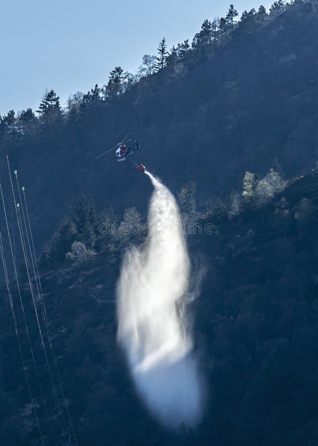 De tricolor-e-n helikopter bestrijdt een wilde brand door water op het te laten vallen stock fotografie
