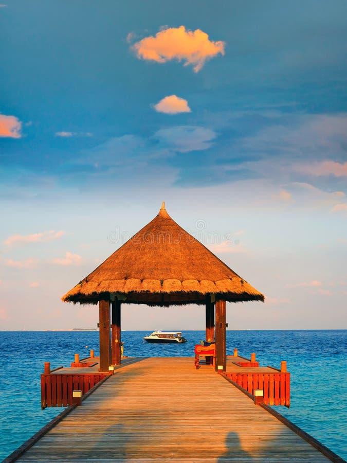 De tropische met stro bedekte zonsondergang van het dakpaviljoen, de Maldiven royalty-vrije stock foto