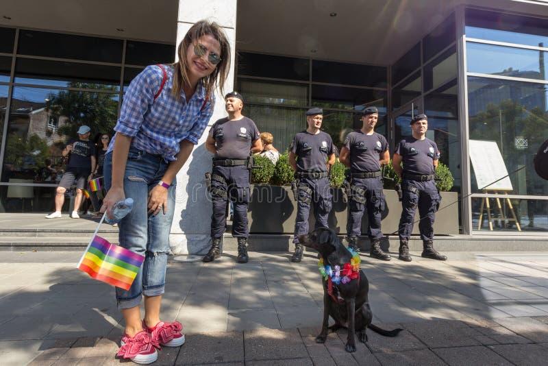 De Trotsdeelnemer van Belgrado het Vrolijke markeren stellen met haar hond & een homosexueel voor politie De parade gebeurde dit  stock fotografie