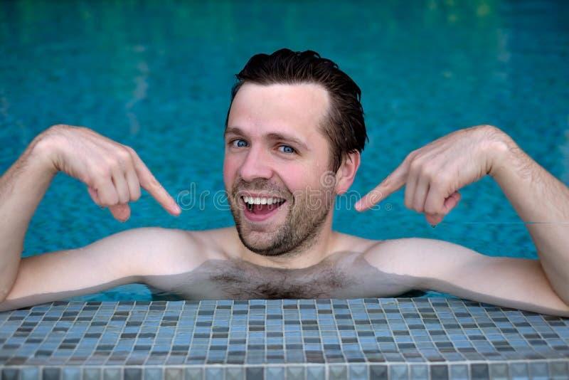 De trotse Kaukasische jonge mens kijkt vooruit tonend met wijsvingers op zich Hij zwemt in pool tijdens vakantie royalty-vrije stock afbeelding