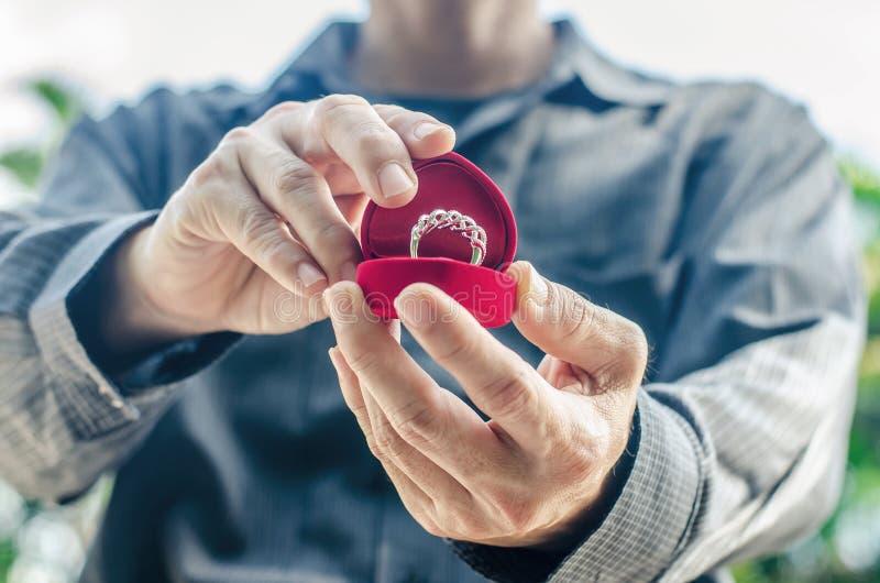 De trouwring in een speciale doos, houdt in de handen van de bruidegom De mens geeft een ring met een diamant in een rode doos stock afbeelding