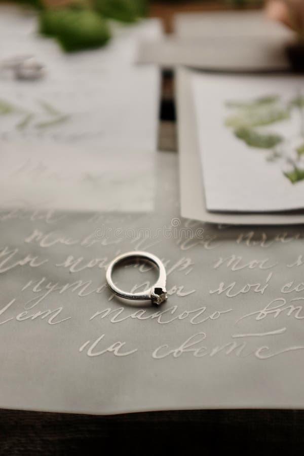 de trouwring ligt op de huwelijksuitnodigingen en de brief aan het decoratieve de brievenontwerp van de bruid hernich kalligrafie royalty-vrije stock afbeeldingen