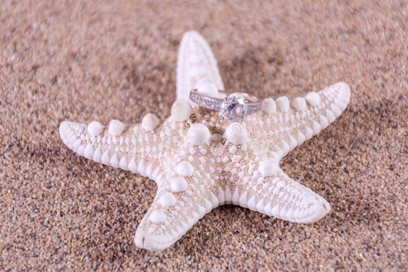 De trouwring van de diamantovereenkomst op zeester op zandig strand royalty-vrije stock afbeelding