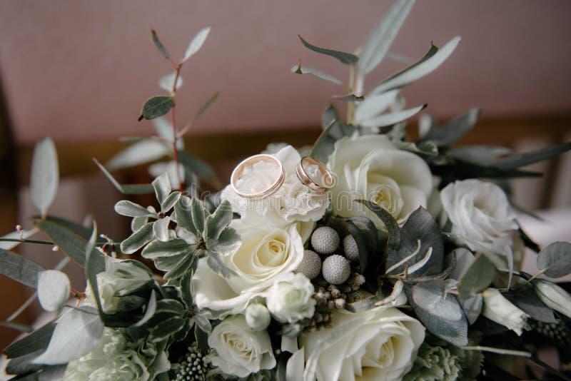 De trouwringen liggen op bloem dichte omhooggaand royalty-vrije stock afbeelding