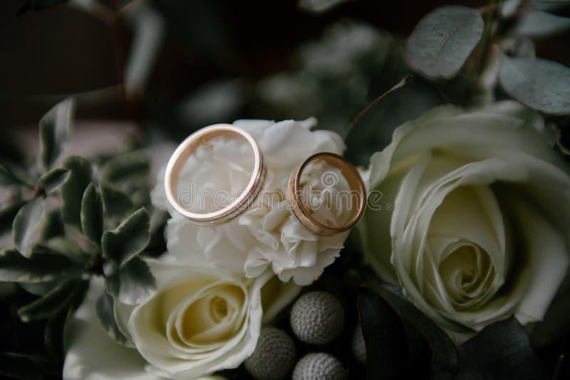 De trouwringen liggen op bloem dichte omhooggaand stock fotografie