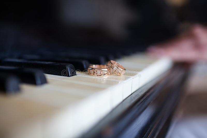 De trouwringen liggen op de pianosleutels stock foto's