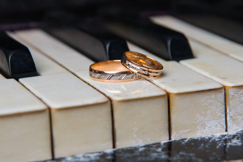 De trouwringen liggen op zwart-witte sleutels van de piano stock foto