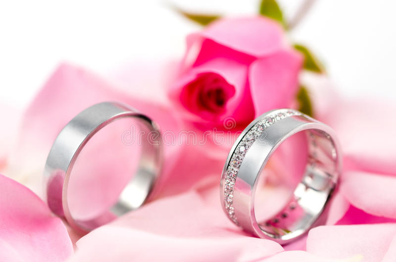 De trouwringen op roze doorbladert stock fotografie