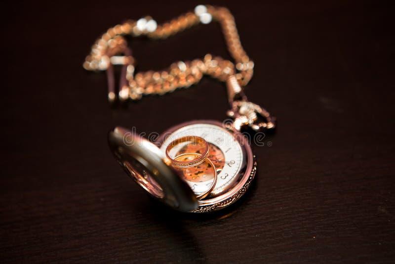 De trouwringen zijn op het horloge stock afbeeldingen