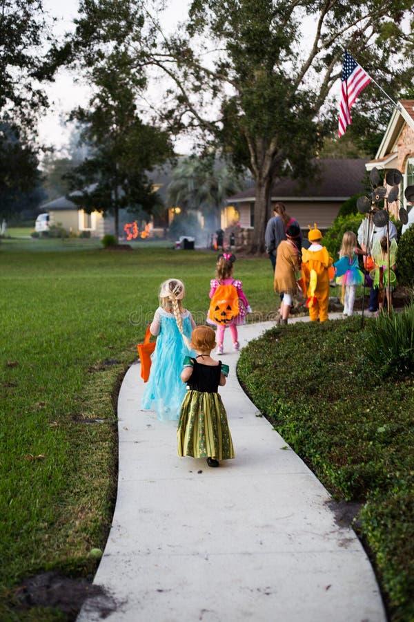 De truc van Halloween en van jonge geitjes of het behandelen van huis-aan-huis het gaan bij nacht royalty-vrije stock fotografie