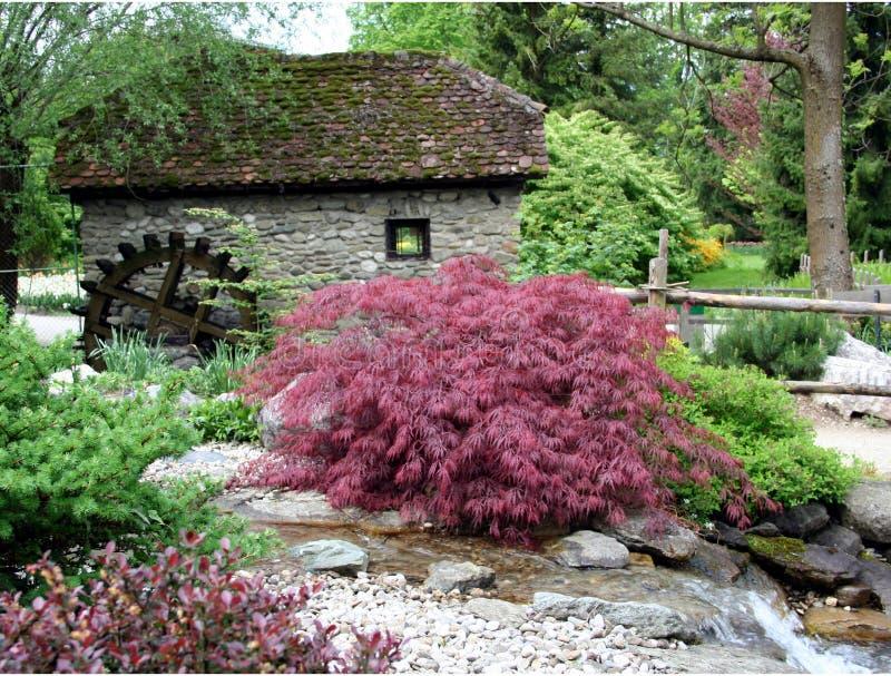 De tuin en de watermolen van het water stock afbeeldingen