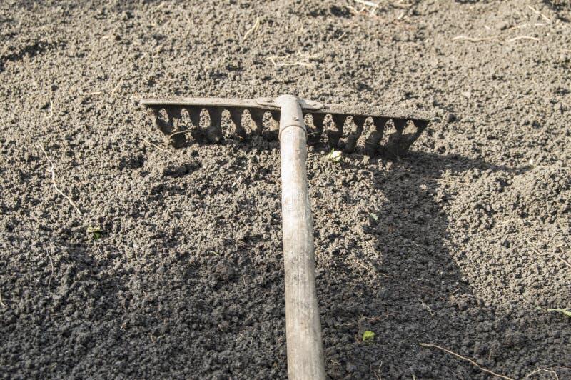 De tuin harkt het liggen op de geploegde bovengrond voor het planting-concept het tuinieren, de lente die, zonnelicht tuinieren royalty-vrije stock fotografie