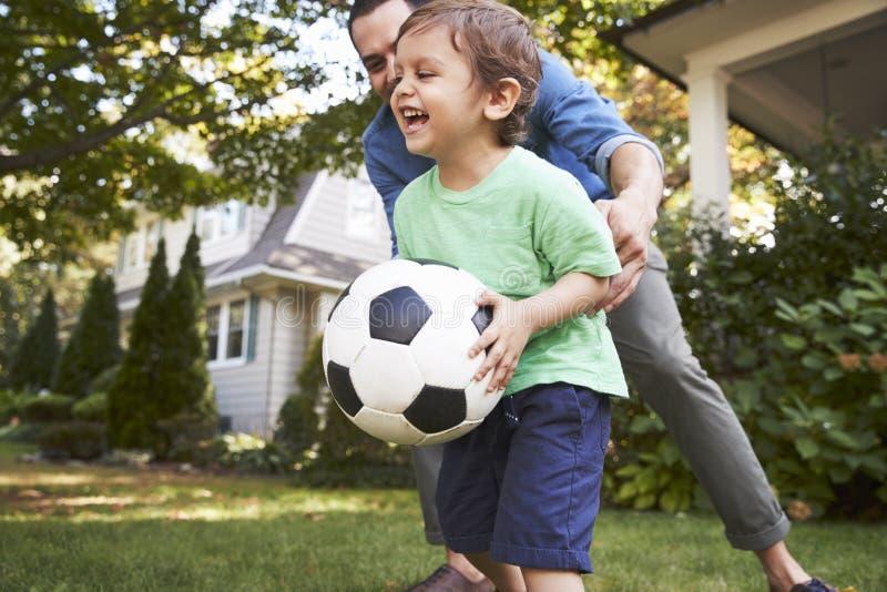 De Tuin van vaderplaying soccer in met Zoon royalty-vrije stock fotografie