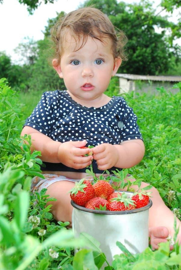 De tuinbedden dichtbij het meisje zit, en dichtbijgelegen is het stock fotografie