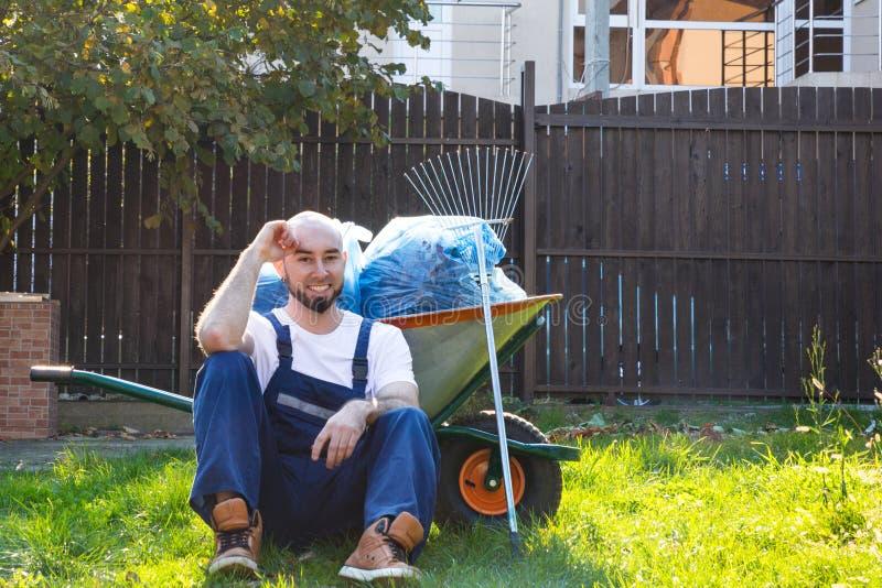 De tuinman in blauwe eenvormig rust op het gras Glimlach en goede stemming Tuinlevering op de achtergrond royalty-vrije stock foto