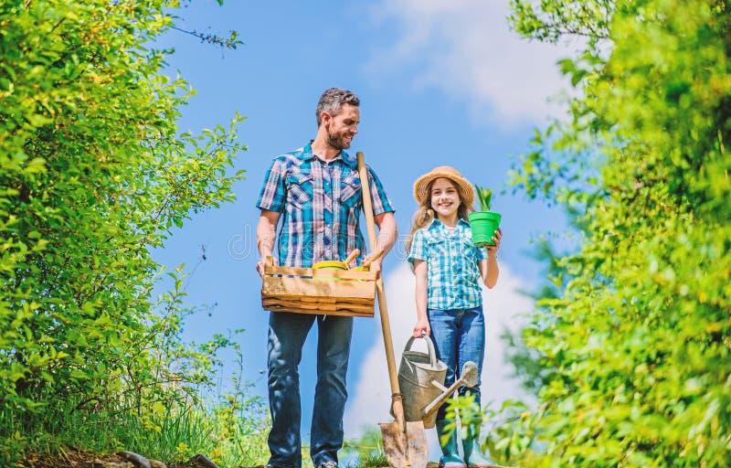 De tuinwerken De tuin van de lente Vader en dochter van de de lente de de tuinierende controlelijst met schop en gieter in tuin H stock fotografie