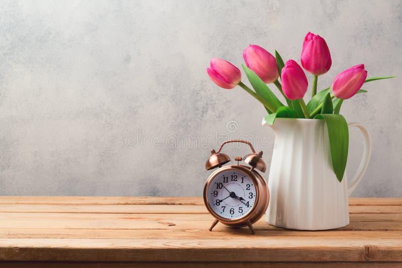 De tulp bloeit boeket en retro wekker stock foto