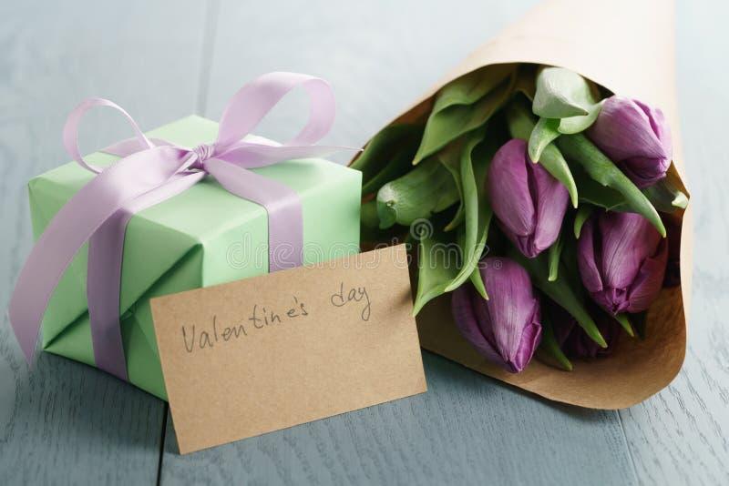 De tulp bloeit met groene giftvakje en document kaart op blauwe houten lijst voor valentijnskaartendag stock foto's