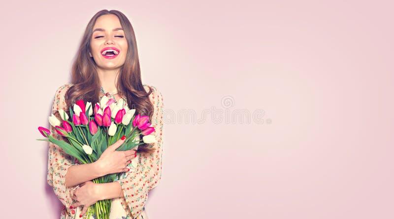 De tulpen van de de holdingslente van het schoonheidsmeisje Gelukkige mooie vrouw die een boeket van kleurrijke tulpen ontvangen stock foto