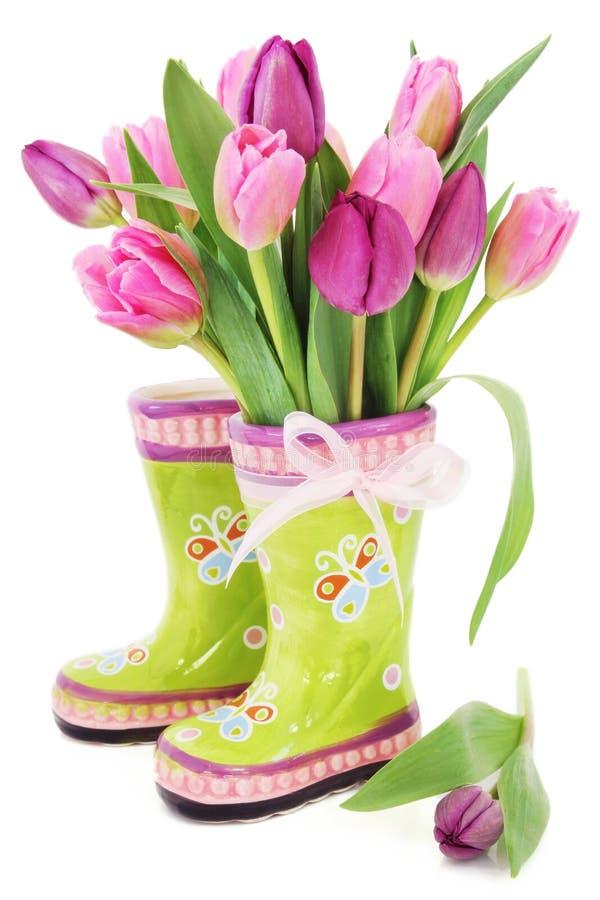 De tulpenbloemen van de lente in laarzen stock foto