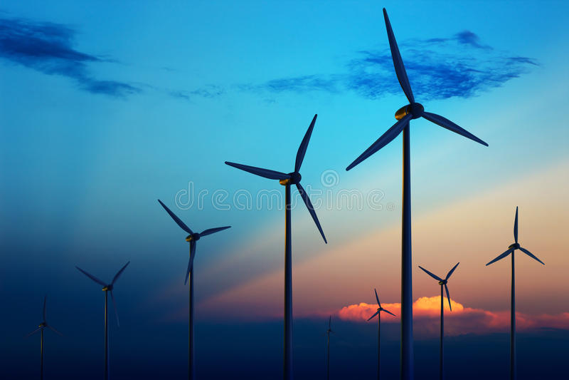 De turbinelandbouwbedrijf van de wind bij zonsondergang stock foto's