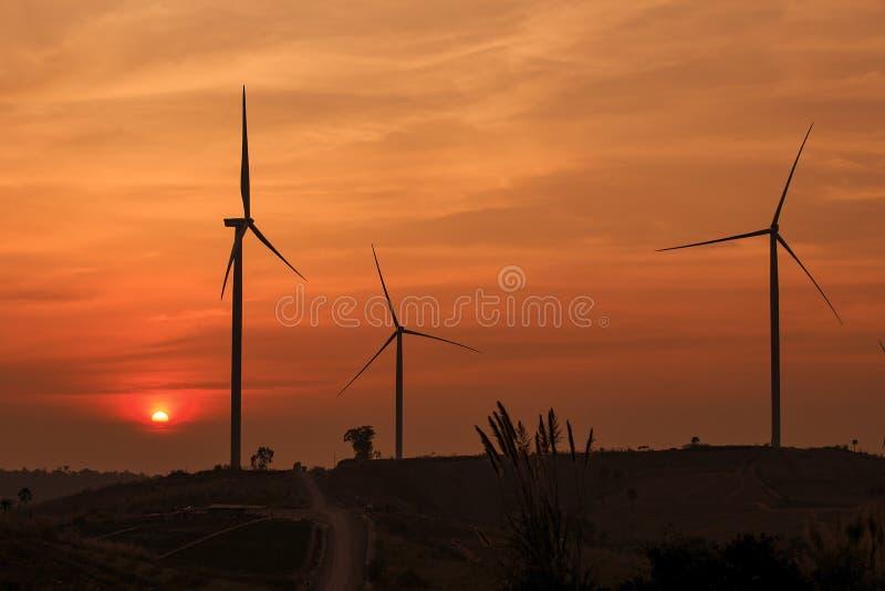 De turbinelandbouwbedrijf van de silhouetwind over moutain met oranje zonsondergang en stock foto's