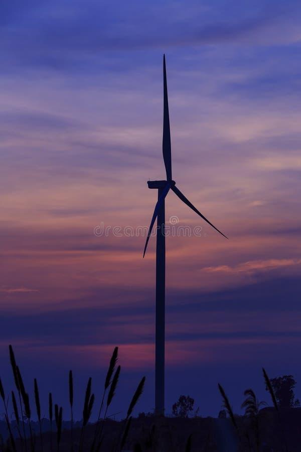 De turbinelandbouwbedrijf van de silhouetwind over moutainwolk in blauwe schemering stock foto's