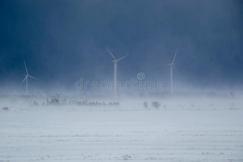 De turbines van de alternatieve energiewind in een sneeuwonweer stock foto's