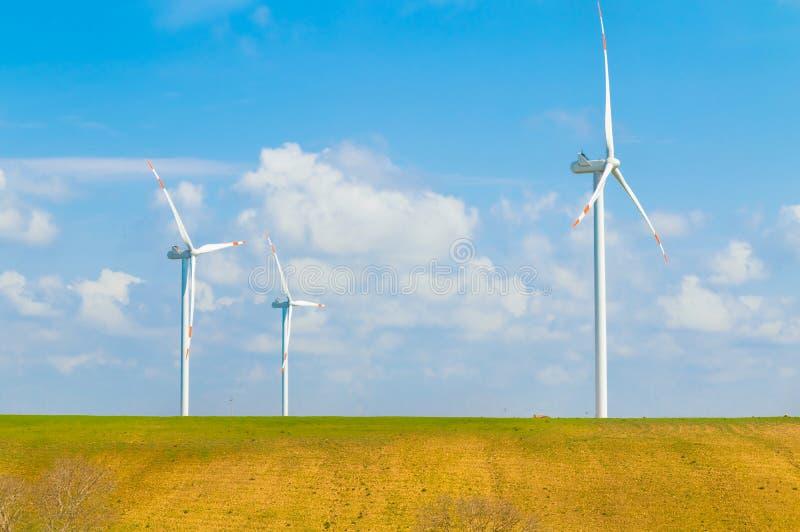 De turbines van de windenergie zijn één van de schoonste, vernieuwbare stroombron, onder blauwe hemel met witte wolken stock foto