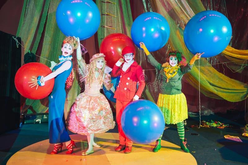 De turner van de close-upclown, die op zijn handen lopen Een groep clowns in make-up met reusachtige gekleurde ballons royalty-vrije stock fotografie