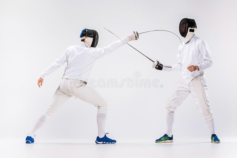 De två männen som bär fäktning, passar övning med svärdet mot grå färger arkivbild