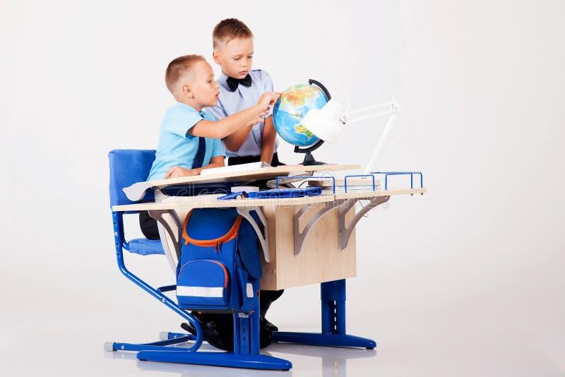 De två pojkarna lär jordklotet för skrivbord på skolan royaltyfri foto