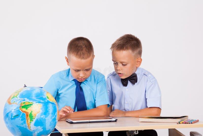 De två pojkarna ser internetminnestavlaskolan royaltyfri bild