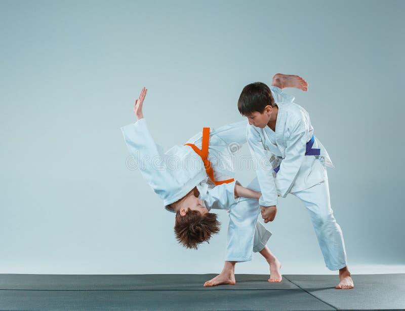 De två pojkarna som slåss på Aikidoutbildning i kampsportskola Sund livsstil och sportbegrepp arkivfoton