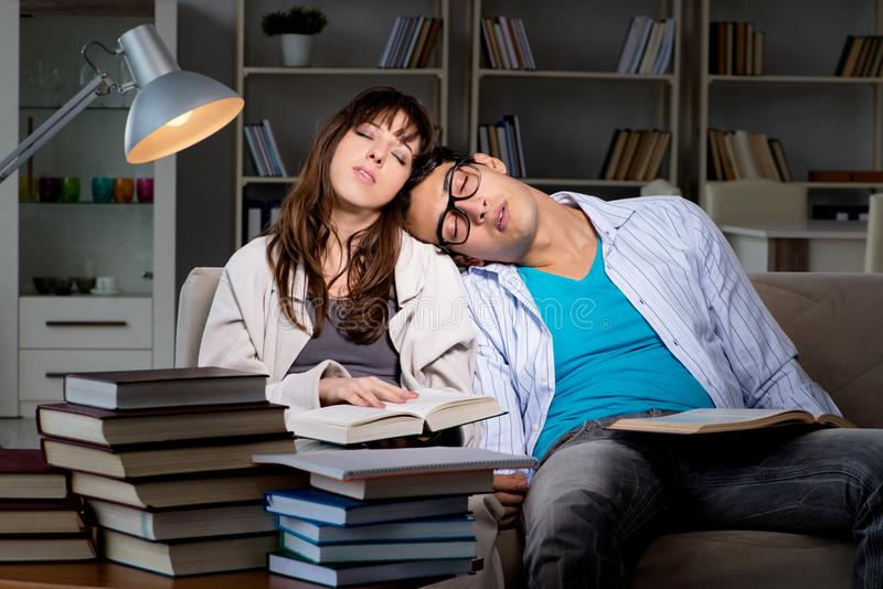 De två studenterna som studerar sent att förbereda sig för examina royaltyfri foto