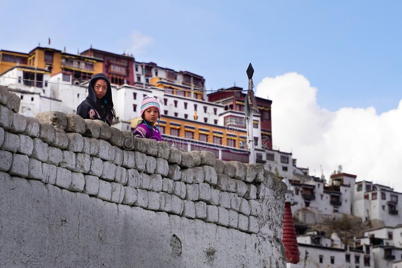 De två tibetana flickorna som blir och ser från väggen royaltyfri fotografi