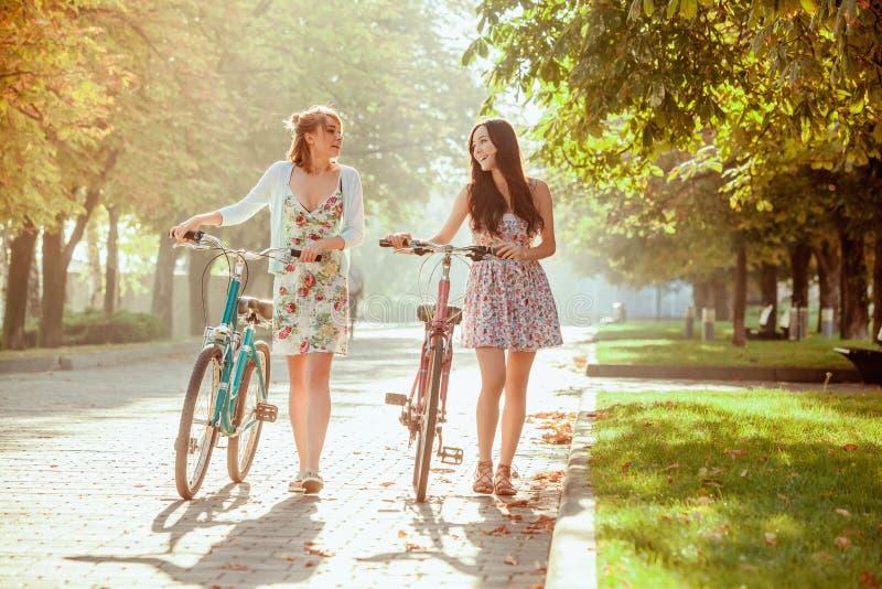 De två unga flickorna med cyklar parkerar in royaltyfri fotografi