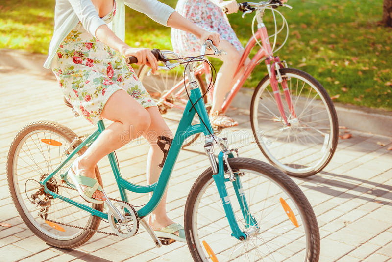 De två unga flickorna med cyklar parkerar in arkivfoton