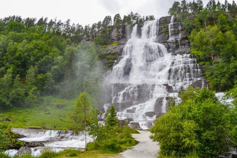 De Tvindefossenwaterval is een schitterende 152m waterval die dichtbij Voss in bundels met een bevallig karakter tuimelen Populai stock fotografie