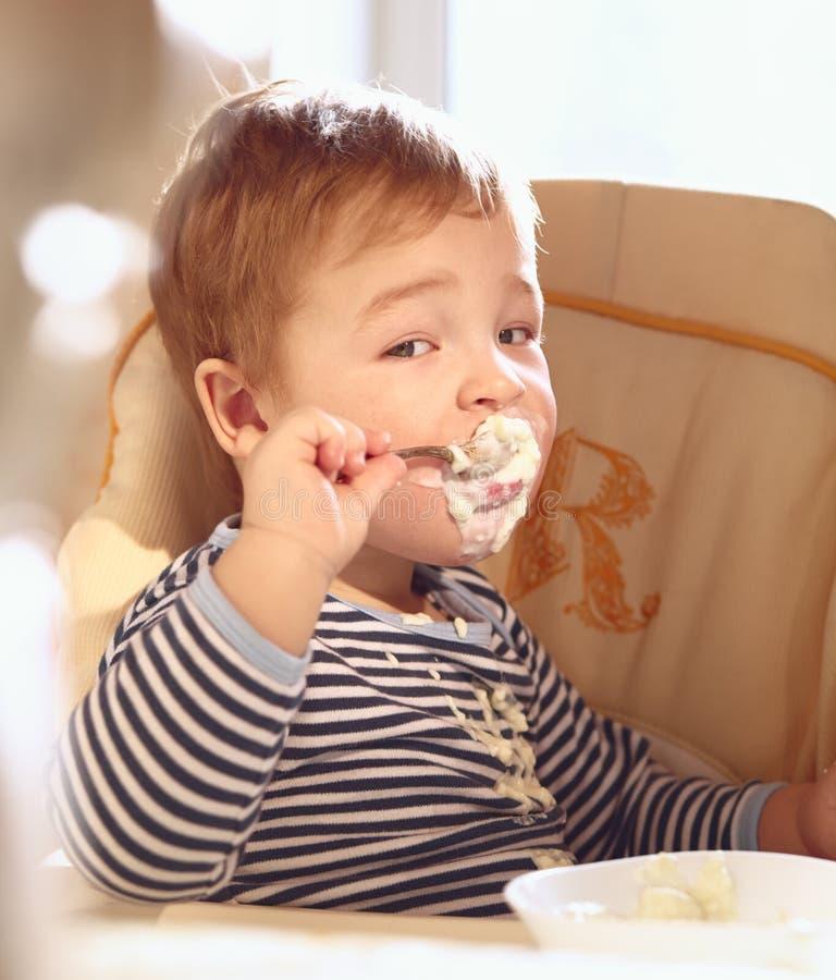 De twee éénjarigenjongen eet havermoutpap in de ochtend. stock fotografie