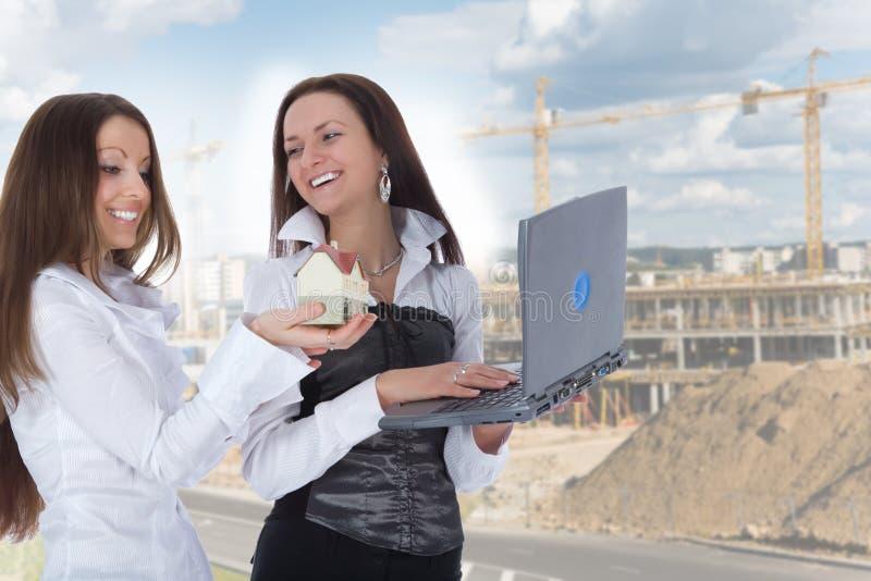 De twee bedrijfsvrouw adverteert onroerende goederen stock foto's