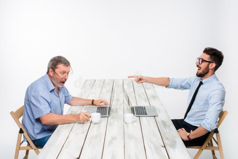 De twee collega's die op kantoor aan witte achtergrond samenwerken stock foto