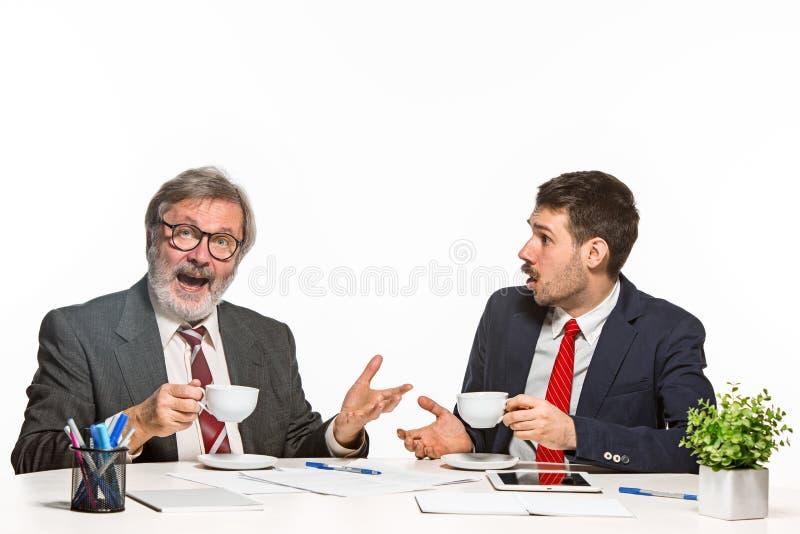 De twee collega's die op kantoor aan witte achtergrond samenwerken stock afbeelding