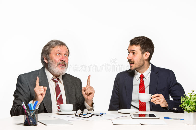 De twee collega's die op kantoor aan witte achtergrond samenwerken royalty-vrije stock afbeeldingen