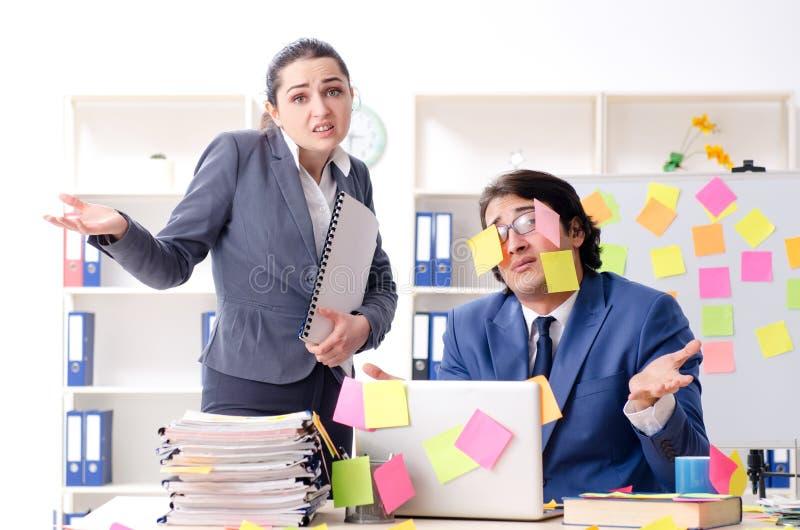 De twee collega'swerknemers die in het bureau werken stock fotografie