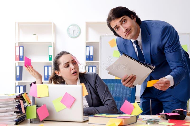 De twee collega'swerknemers die in het bureau werken stock afbeeldingen