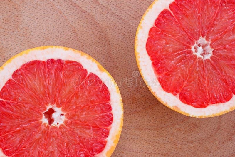 De twee die helften van grapefruit worden gesneden stock afbeeldingen