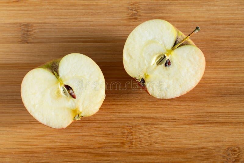 De twee helften van een appel op een houten achtergrond Hoogste mening royalty-vrije stock fotografie
