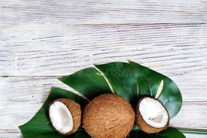 de twee helften van kokosnoot en ??n gehele kokosnoot met een blad van tropische monstera planten op een witte houten achtergrond royalty-vrije stock afbeeldingen